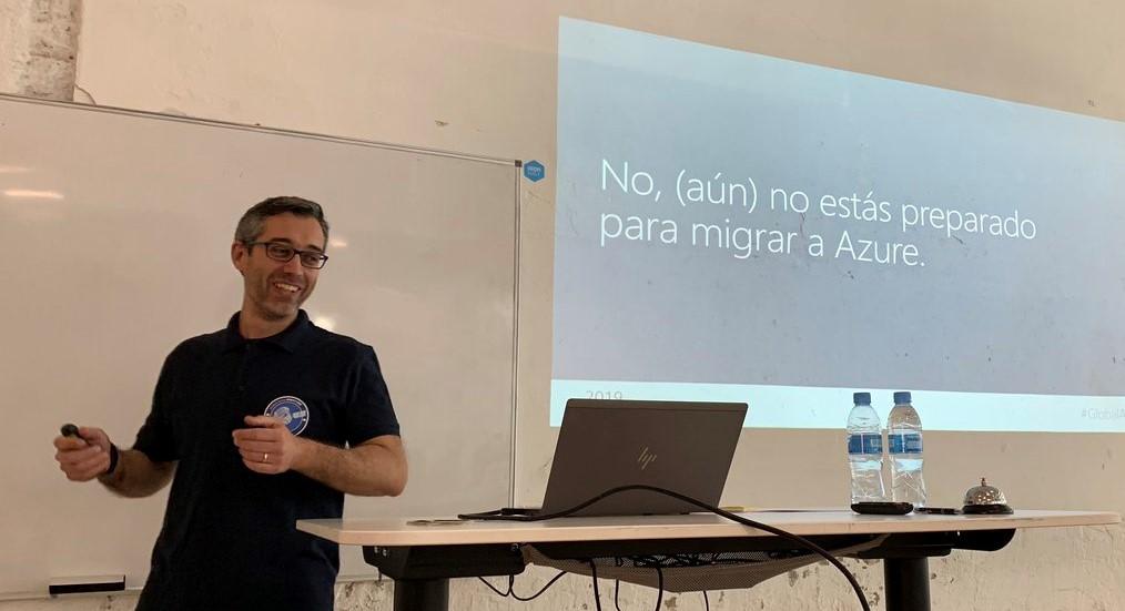 Yo mismo dando la charla del Azure Bootcamp. Se ve la presentación proyectada en la pared, con el título de la charla.